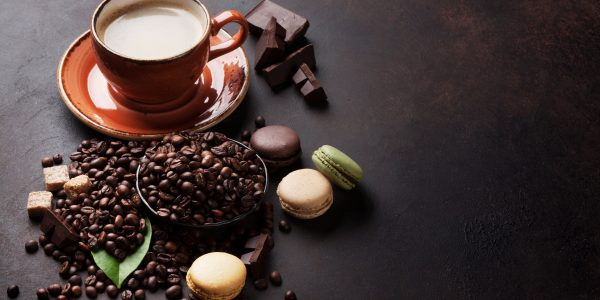 Coffee cup, beans and ground powder, chocolate and macaroons on stone background. With copy space for your text